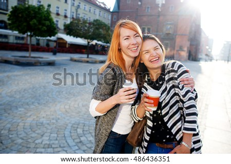 Two cute young women standing on the square of the beautiful European city. They are holding a paper cups of coffee and a hug. Girlfriends are glad to a meeting. They laugh.