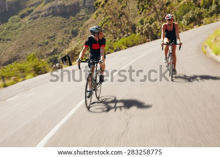 Two cyclist practicing for triathlon race. Triathletes practicing cycling on country road. Man and woman riding bicycle on open road. - stock photo