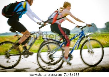 two cyclists biking in motion - stock photo