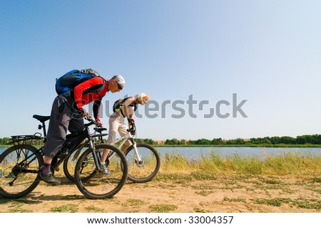 two cyclists biking outdoors - stock photo