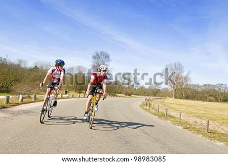 Two cyclists discussing the tactics of their escape, now leading the race - stock photo
