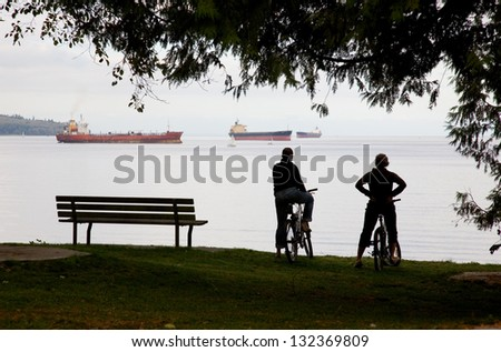 two cyclists in Stanley park take a break and admire the ships across English Bay in Vancouver, British Columbia, Canada. - stock photo