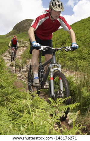 Two cyclists on countryside track against hill and sky - stock photo