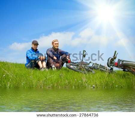 two cyclists on river bank - stock photo