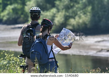 Two cyclists on the Thames river bank reading a map - stock photo