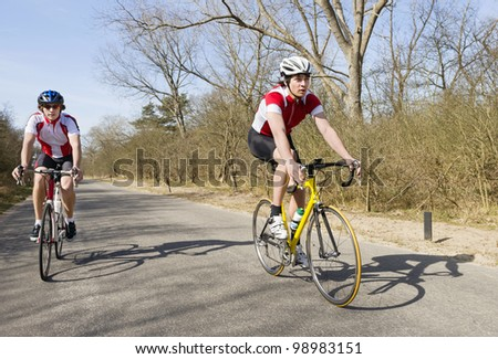 Two cyclists overtaking on a small rural road - stock photo