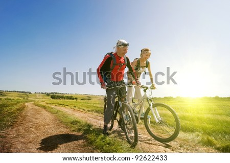 two cyclists relax biking outdoors - stock photo