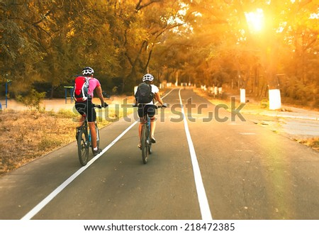 Two cyclists riding on road  - stock photo