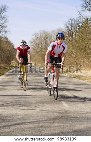 Two Cyclists straining themselves, climbing up a hill on a bicycle - stock photo
