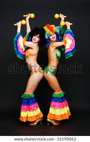 two dancers in bright costumes over dark background - stock photo