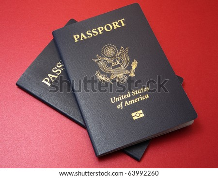 Two dark blue United States passports arranged on a fine textured red background material - stock photo