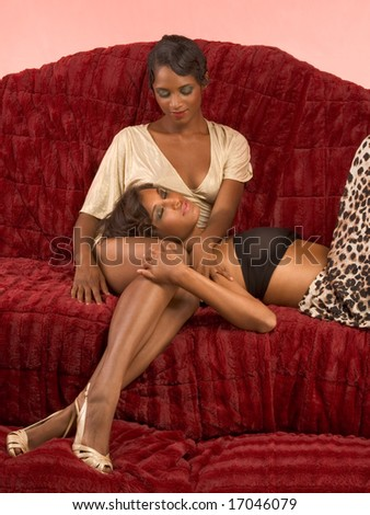 Two dark skinned sensual female lovers petting on couch (retro style) - stock photo