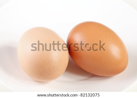 Two darker and lighter brown colored eggs - stock photo
