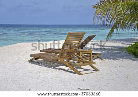 Two deck chairs in front of the ocean with selective focus on one chair and leaf of palm tree