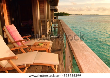 Two deck chairs on a sea view balcony at a tropical resort in Maldives. - stock photo
