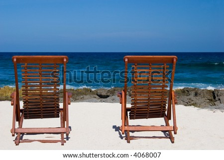 Two deck chairs on a tropical beach - stock photo