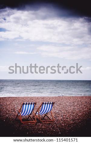 Two deck chairs on Brighton beach - stock photo