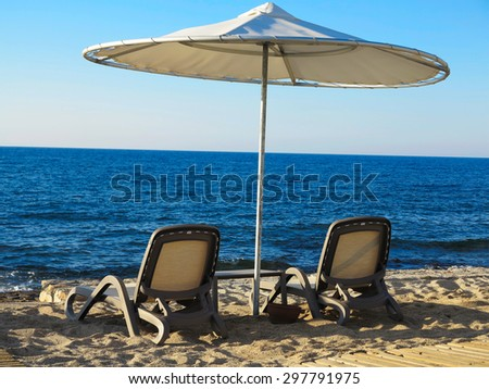 Two deckchairs and umbrella on the blue sea sand beach - stock photo