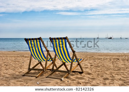 Two deckchairs on a sandy beach - stock photo
