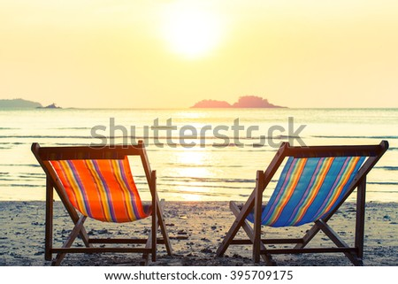 Two deckchairs on a sunny sea beach.