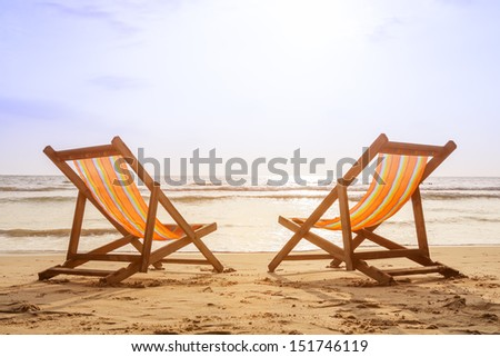 Two deckchairs on the beach at sunset with a tropical sea background - stock photo