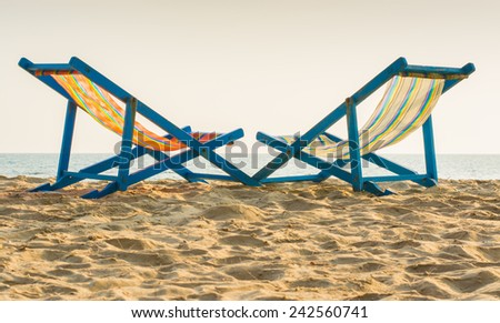 Two deckchairs on the beach with - stock photo