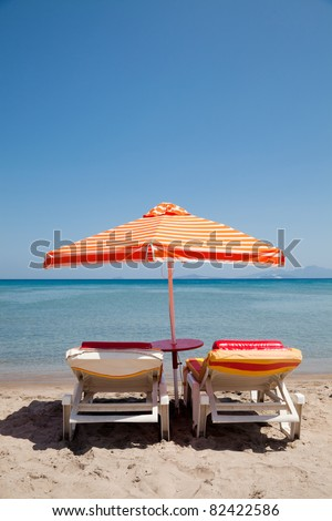 Two deckchairs under parasol on beach in sunny day - stock photo