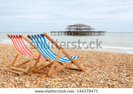 Two deckhairs on Brighton beach with West Pier behind. Brighton, East Sussex, England - stock photo