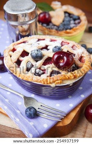 Two decorated homemade shortcrust pastry berry pies with polka dot cloth, shiny metal icing sugar shaker, fork and selection of berries on grunge style wooden table. - stock photo