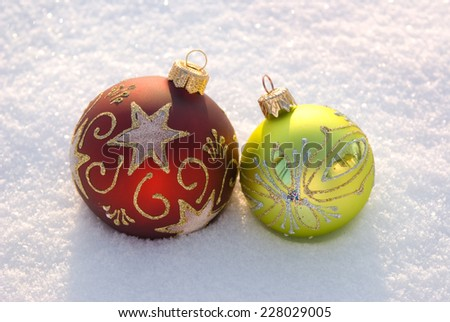 Two decorative spheres on a white snow. - stock photo