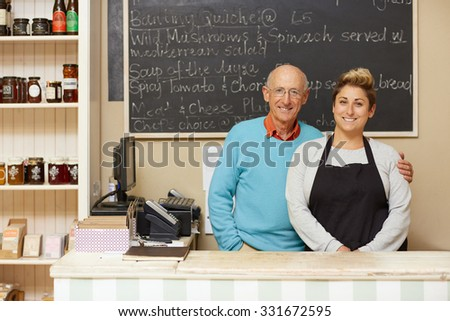 Two deli employees behind the counter - stock photo