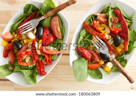 Two delicious bowls of baby spinach and cayenne or chili pepper salad served as individual appetizers or accompaniments to a healthy meal, overhead close up view - stock photo