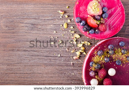 Two delicious cakes with fresh berries, raspberries, blueberry, currants and pistachios on black background. Free space for your text. - stock photo