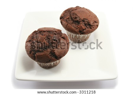 two delicious chocolate chip muffins on a square china plate - stock photo