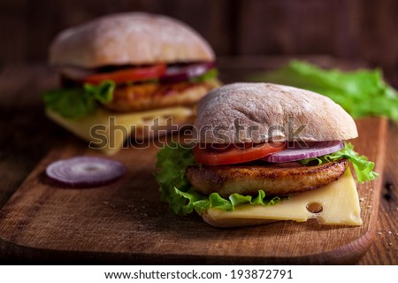 Two delicious ciabatta burgers stacked high with a chicken patty, cheese, fresh lettuce, onion and tomato on a fresh ciabatta standing on brown paper on a wooden tabletop - stock photo