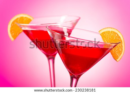 Two delicious cosmopolitan cocktails with cranberry juice, vodka, triple sec, and fresh squeezed lime juice with an orange garnish. - stock photo