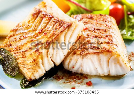 Two delicious fillets of marinated grilled or oven baked pollock or coalfish served with a fresh salad, close up view showing the texture - stock photo