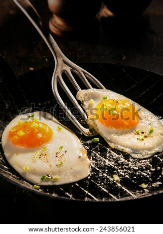 Two delicious free range fried eggs with dark yellow yolks seaoned with salt and aromatic herbs for a healthy breakfast and start to the day - stock photo