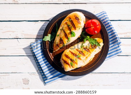 Two delicious fresh grilled chicken breasts seasoned with herbs served on a plate with tomato on a white wood table, overhead view in summer sunshine - stock photo