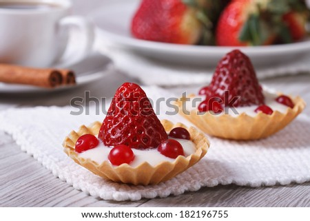 Two delicious fresh strawberry tarts, cranberry and cream on the table. horizontal. close-up   - stock photo