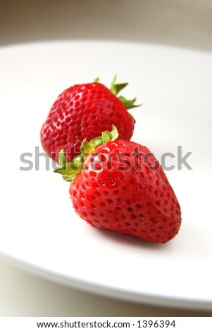 Two delicious strawberries on a white plate with narrow depth of field. - stock photo