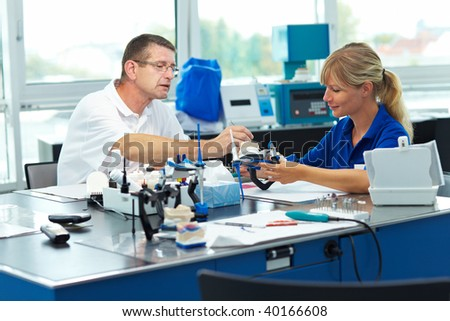 Two dental technicians helping each other in a laboratory