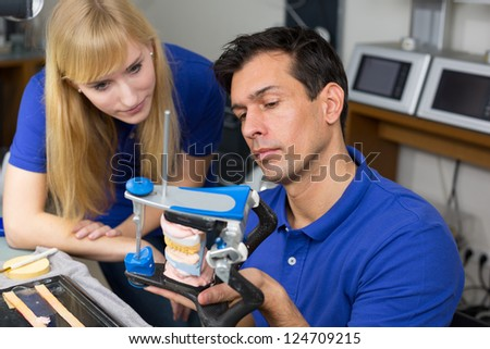 Two dental technicians looking at articulator in a dental lab