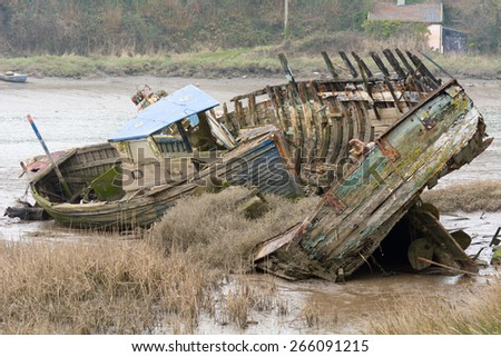 Two derelict rotting wooden boats on River Taw, Fremington, Devon, England - stock photo