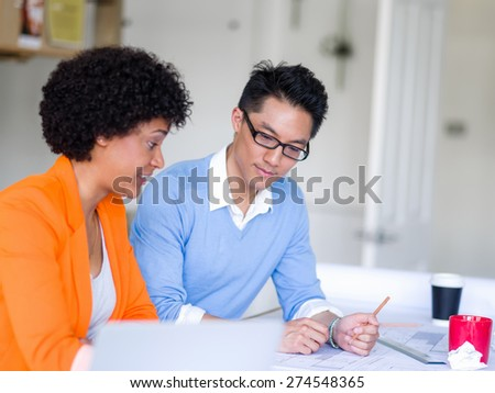 Two desingers working on a project together in office - stock photo