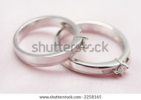 Two diamond wedding rings on a silver satin background