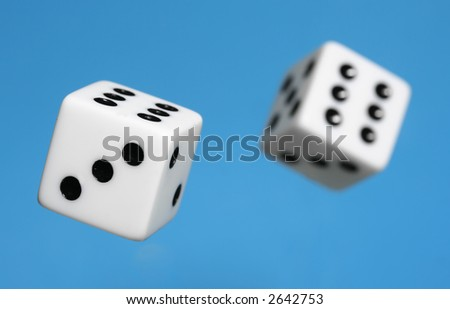 Two Dice being roled - mid air, isolated blue background - shallow depth of field - stock photo