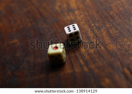 Two dice displaying one and six on a vintage wood plank - stock photo