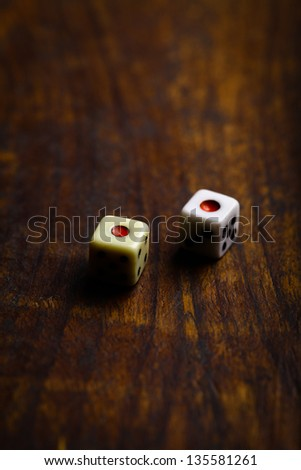 Two dice displaying one on a vintage wood plank - stock photo