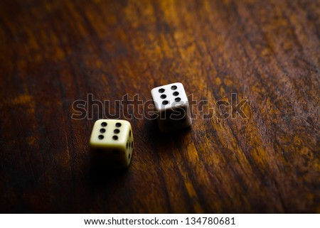 Two dice displaying six on a vintage wood plank - stock photo